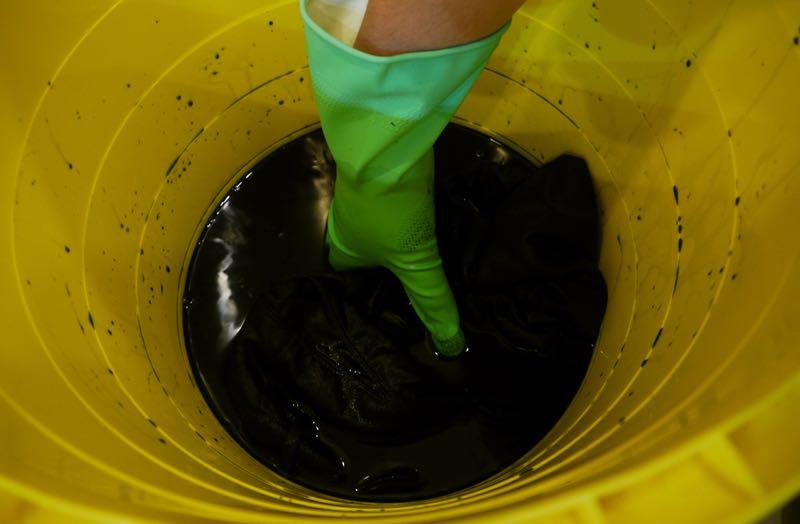 ビニール手袋をはめてパンツをダイロンに浸して混ぜているところ